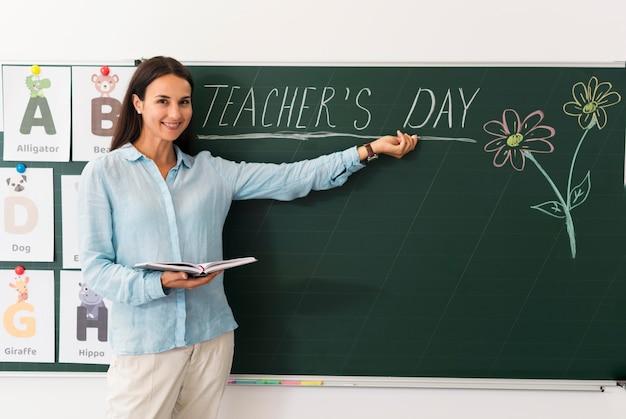 Mujer celebrando el día del maestro con sus alumnos