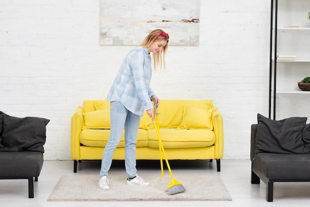 Mujer cepillando la alfombra en casa