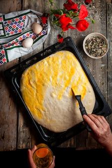 Mujer cepillando la masa con yema de huevo vista superior