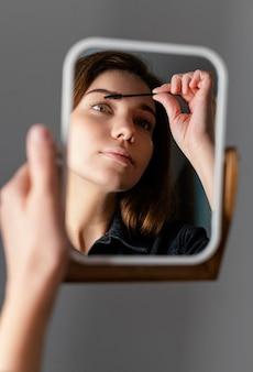 Mujer cepillándose las cejas mientras se mira en el espejo después del tratamiento