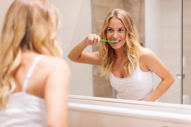 Mujer cepillarse los dientes delante del espejo