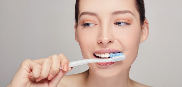 Mujer con un cepillo de dientes en sus manos casi su boca con dientes blancos