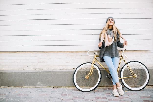 Mujer cerca de bicicleta mirando hacia arriba