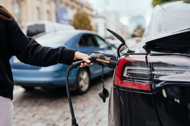 Mujer cerca de coche eléctrico. vehículo cargado en la estación de carga.