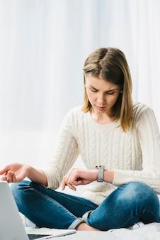 Mujer cerca de la computadora portátil mirando el reloj