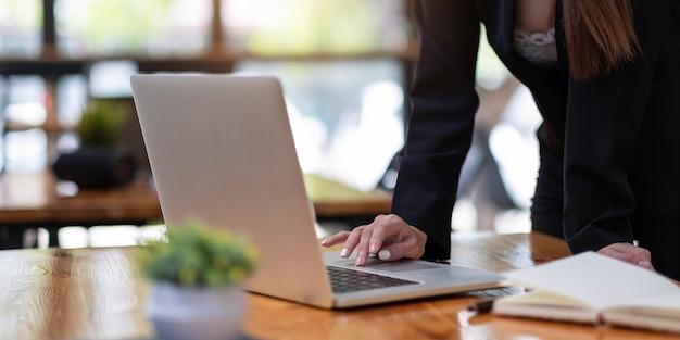 Mujer de cerca con ordenador portátil en el lugar de trabajo
