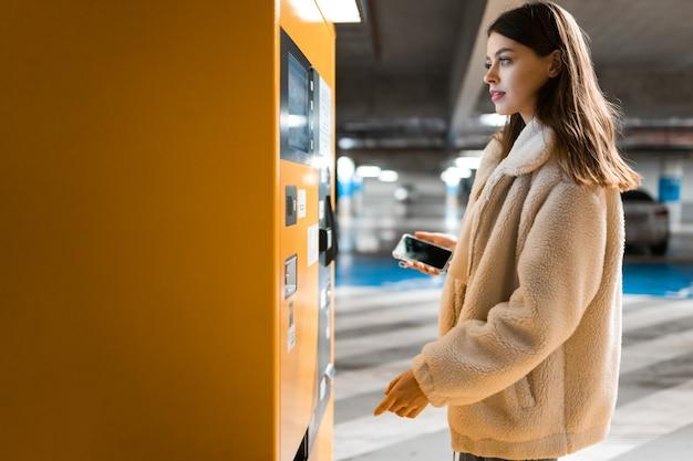 Mujer cerca de la terminal en el estacionamiento subterráneo