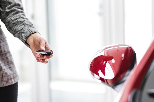 Mujer cerrando el auto de la llave