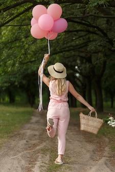 Mujer con una cesta de mimbre, sombrero, globos rosados y flores caminando en un camino rural