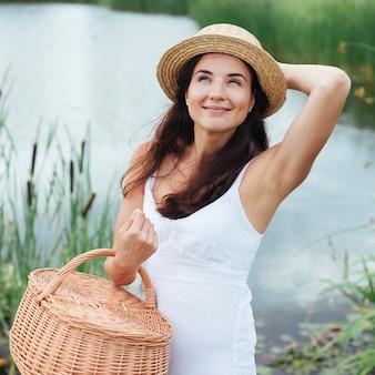 Mujer con cesta de picnic posando junto al lago