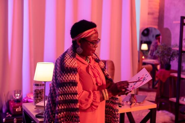 Mujer en un chal. afroamericano regordete adivino vistiendo un chal de lana brillante trabajando en carta natal