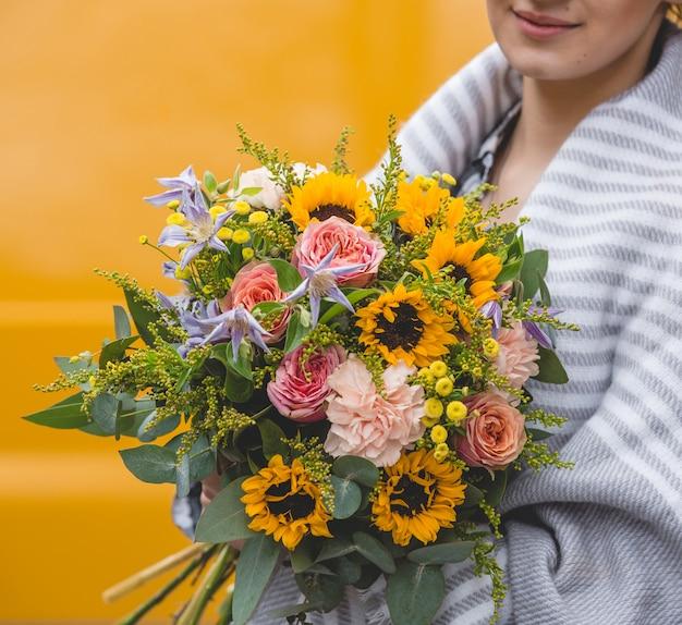 Mujer con chal sosteniendo un ramo de flores en fondo amarillo
