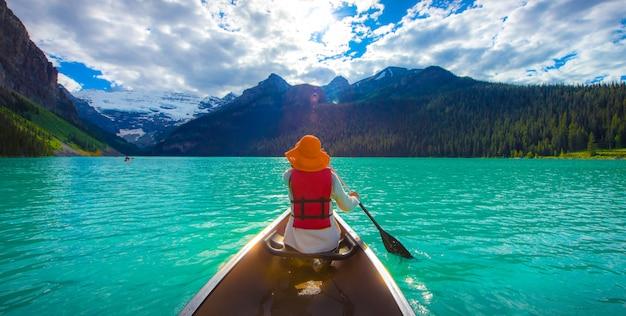 Una mujer con un chaleco salvavidas rojo en canoa en lake louise con un lago de color turquesa y un bluesky.