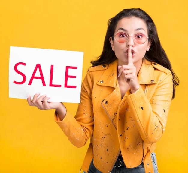 Mujer de chaqueta amarilla ventas gesto silencioso