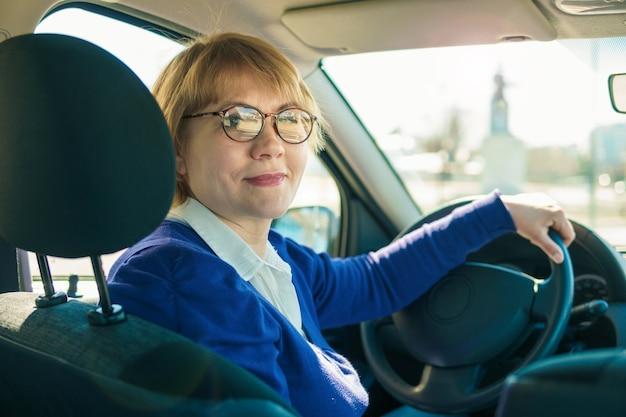 Una mujer con una chaqueta azul conduciendo un automóvil atravesando la ciudad.