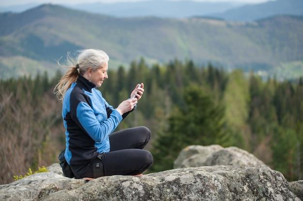 Mujer en una chaqueta azul sentada en el acantilado de la roca y sosteniendo un teléfono móvil