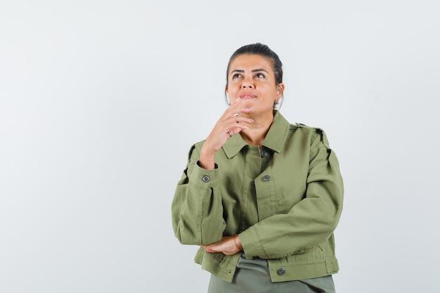 Mujer con chaqueta, camiseta mirando hacia arriba y mirando soñadora