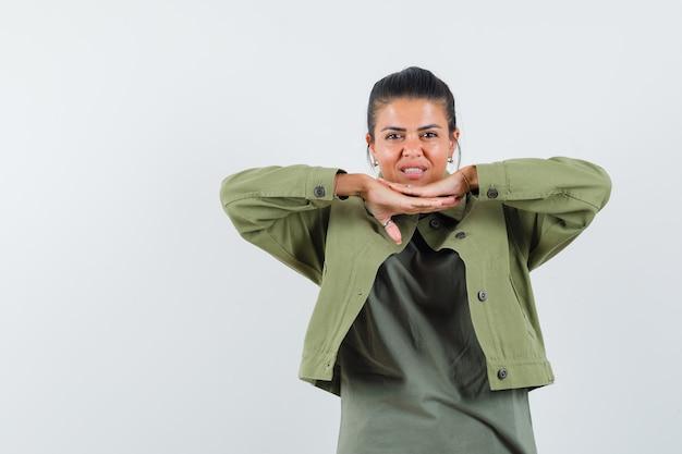 Mujer en chaqueta, camiseta tomados de la mano debajo de la barbilla y luciendo linda