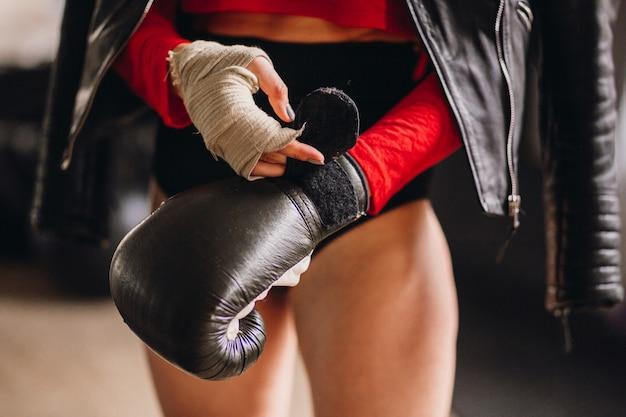 Mujer en chaqueta de cuero se pone guantes de boxeo
