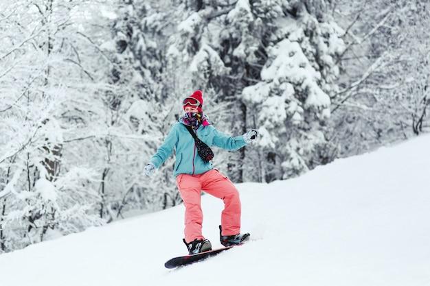La mujer en la chaqueta de esquí azul y los pantalones rosados se coloca en el snowboard en algún lugar en bosque del invierno