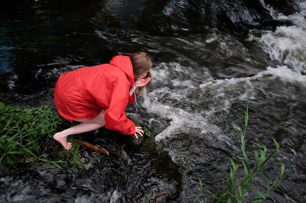 Mujer en chaqueta impermeable roja bebiendo agua del río de montaña