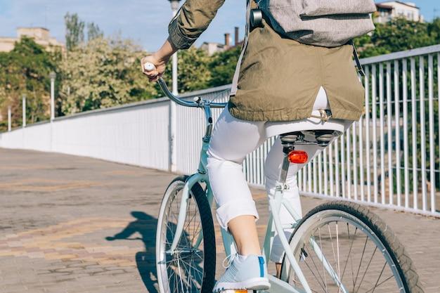 Mujer en chaqueta y jeans monta una bicicleta