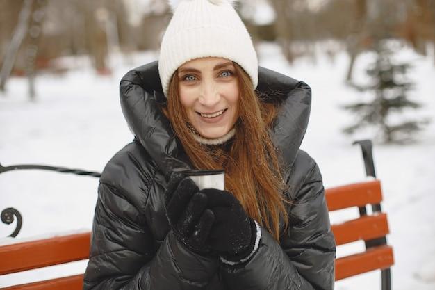 Mujer en una chaqueta negra bebiendo té al aire libre