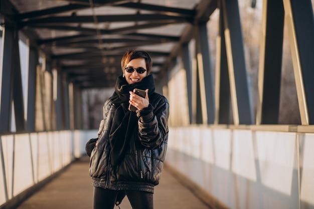 Mujer de chaqueta negra caminando por el puente