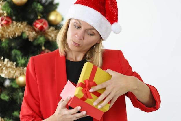Mujer con chaqueta roja y sombrero de santa claus mira en caja de regalo eligiendo regalo para navidad y nuevo