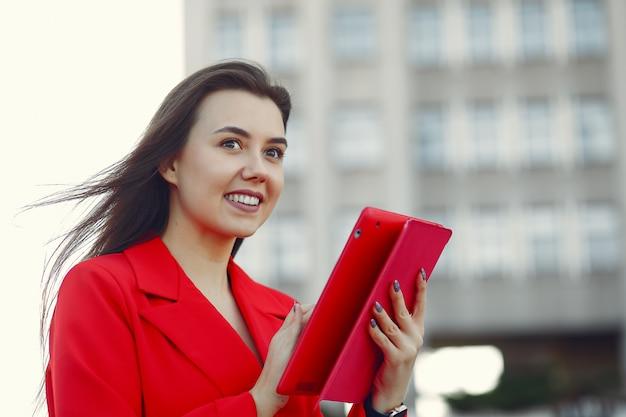 Mujer con chaqueta roja usando una tableta