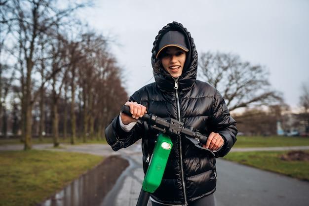 Mujer en una chaqueta en un scooter eléctrico en un parque de otoño.