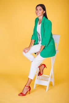 Mujer en la chaqueta verde sentado en la silla sobre fondo amarillo
