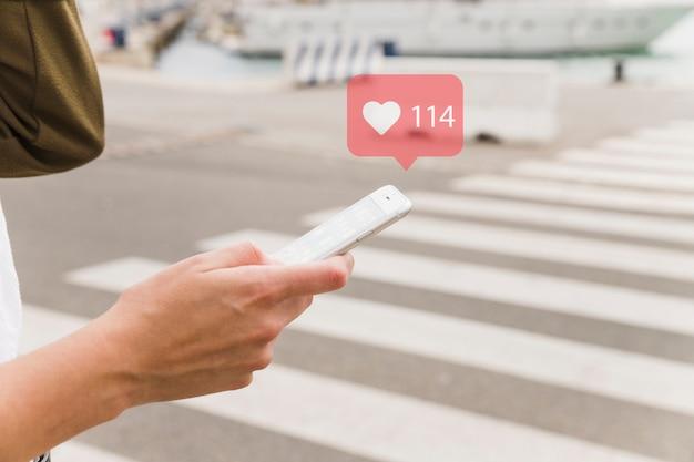 Mujer chateando en el teléfono móvil con el símbolo de forma de corazón