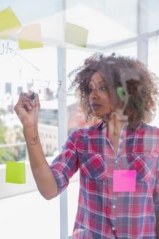 Mujer con check shirt dibujo en diagrama de flujo con marcador