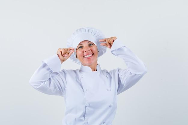 Mujer chef mostrando un cartel de tamaño pequeño en uniforme blanco y con aspecto positivo.