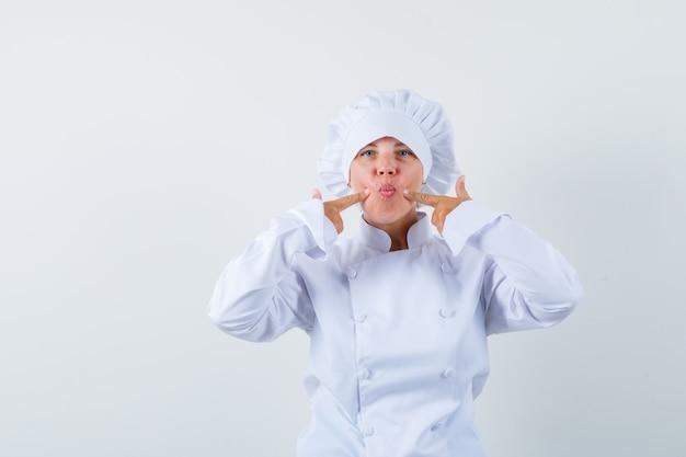 Mujer chef presionando los dedos en las mejillas en uniforme blanco y mirando divertido