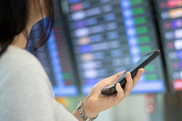 Mujer cheque vuelo transporte aplicación de teléfono móvil reserva boleto viaje