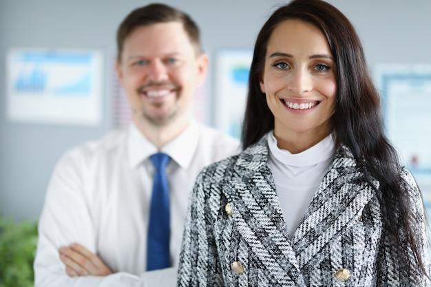 Mujer y chico en ropa de negocios están sonriendo