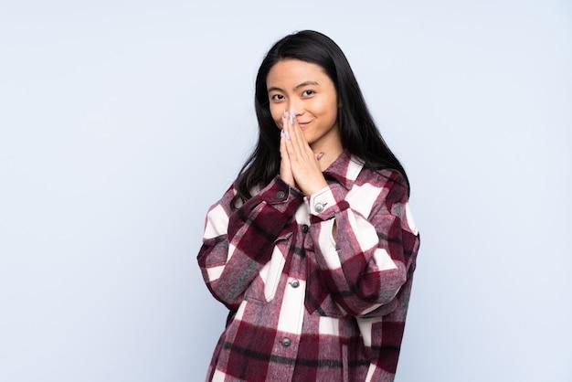 La mujer china del adolescente aislada en fondo azul mantiene la palma unida. la persona pide algo
