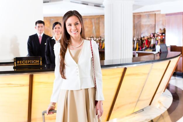 Mujer china asiática que llega a la recepción del hotel de lujo en ropa de negocios con carro