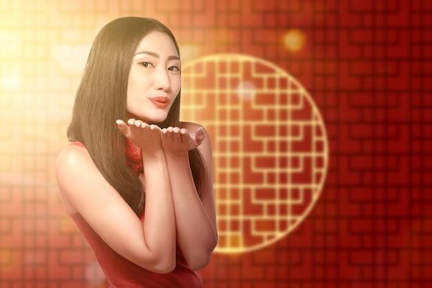 Mujer china asiática en un vestido cheongsam celebra el año nuevo chino