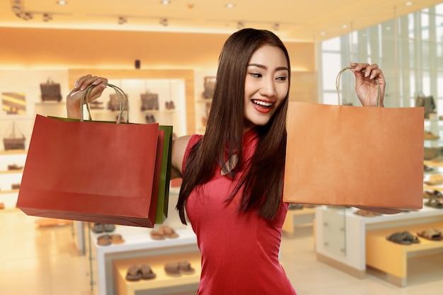 Mujer china en cheongsam vestido con bolsa de compras