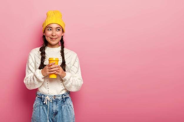 Mujer china de ensueño bebe café para llevar, se levanta pensativamente contra el fondo rosa