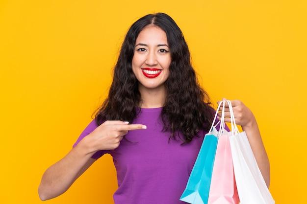Mujer china española con bolsa de compras sobre pared aislada y apuntando