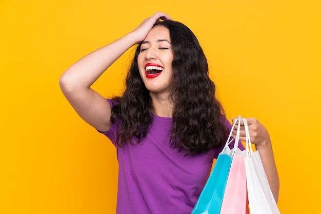 Una mujer china española con una bolsa de compras sobre una pared aislada se ha dado cuenta de algo y tiene la intención de encontrar la solución