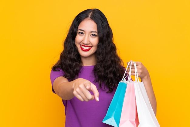 Mujer china española con bolsa de compras sobre pared aislada señala con el dedo con una expresión segura