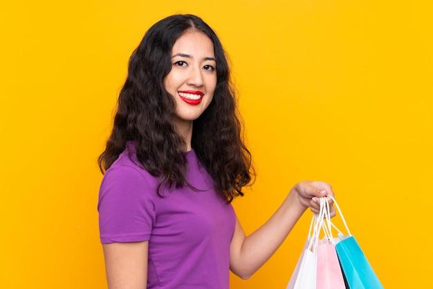 Mujer china española con bolsa de compras sobre pared aislada sonriendo mucho