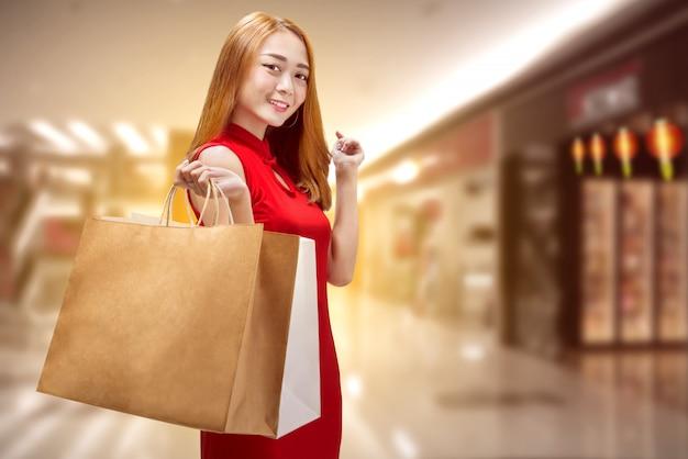 Mujer china feliz con la ropa tradicional que sostiene bolsos de compras