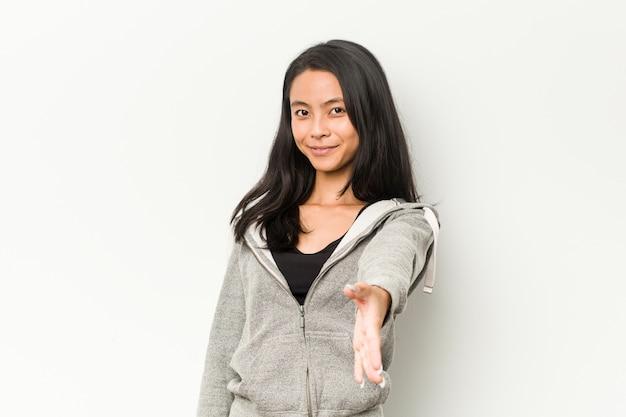 Mujer china fitness joven estirando la mano a la cámara en gesto de saludo.