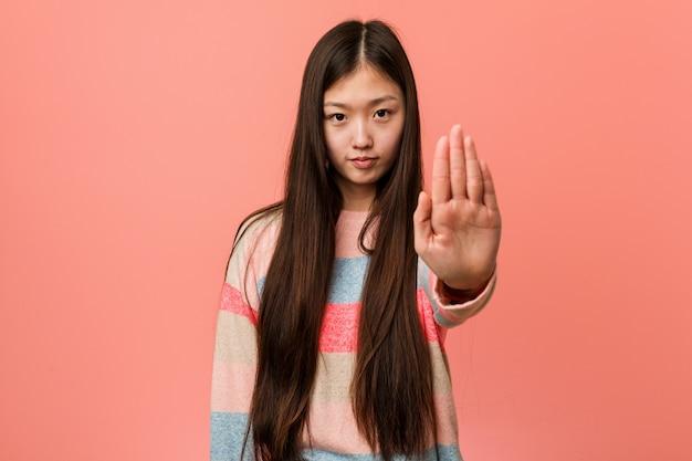 Mujer china fresca joven que se coloca con la mano extendida que muestra la señal de stop, previniéndole.